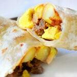breakfast burrito cut in half on white plate