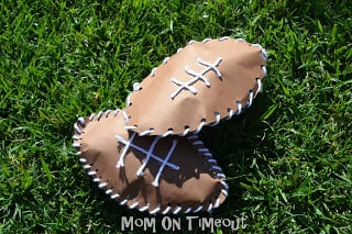 paper footballs made with brown construction paper and yarn on grass