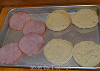 canadian bacon and english muffins on baking sheet