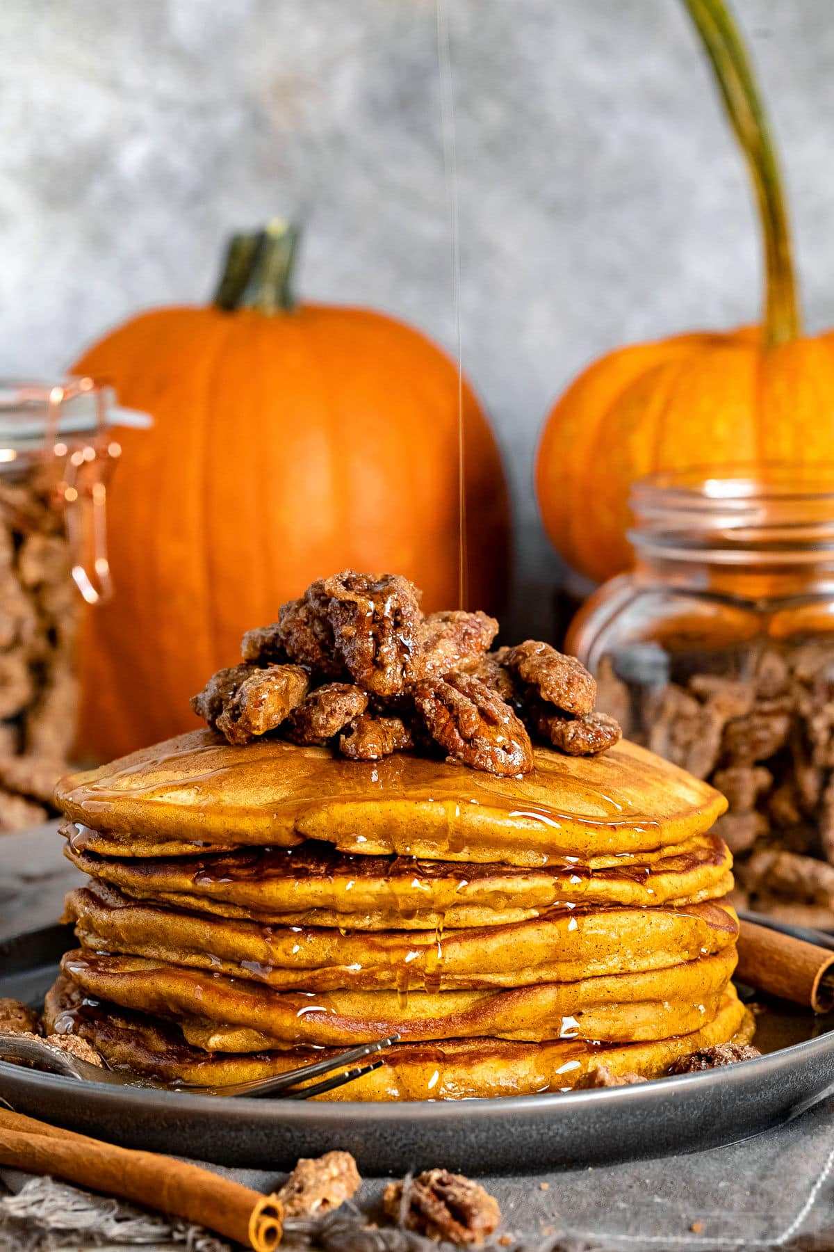 stack of pumpkin pancakes with candied pecans on top and syrup being drizzled onto pancakes with pumpkins in the background