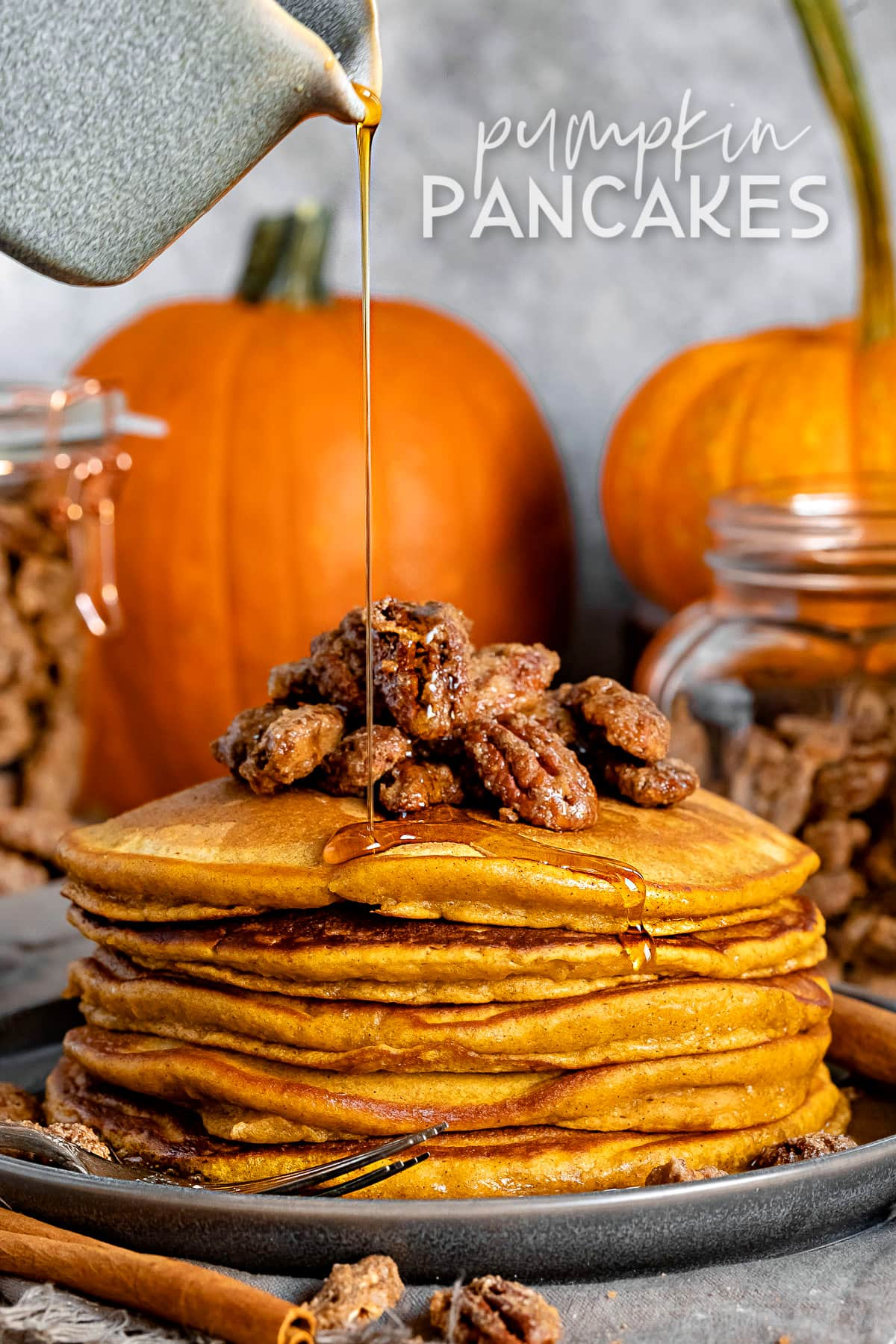 stack of pumpkin pancakes with candied pecans on top and syrup being drizzled onto pancakes