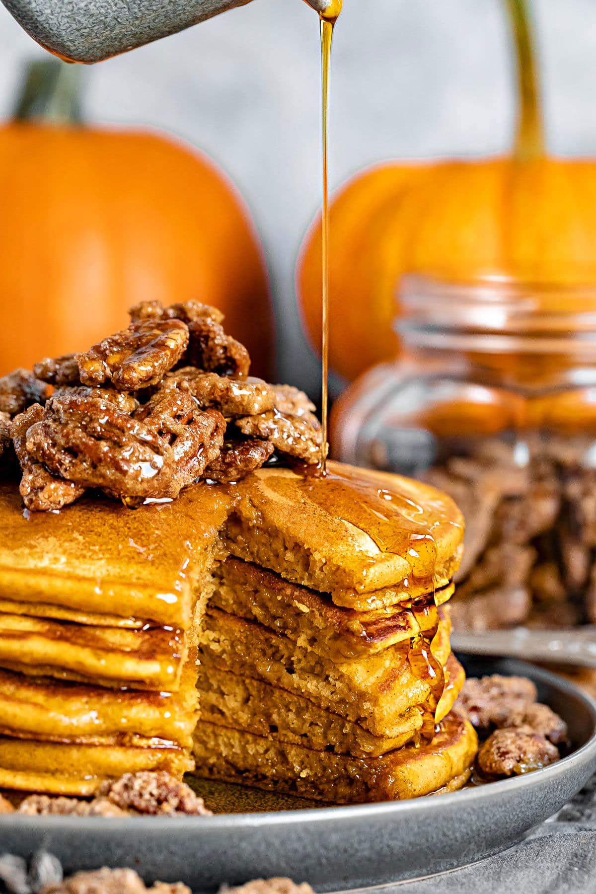syrup being poured on stack of pumpkin pancakes
