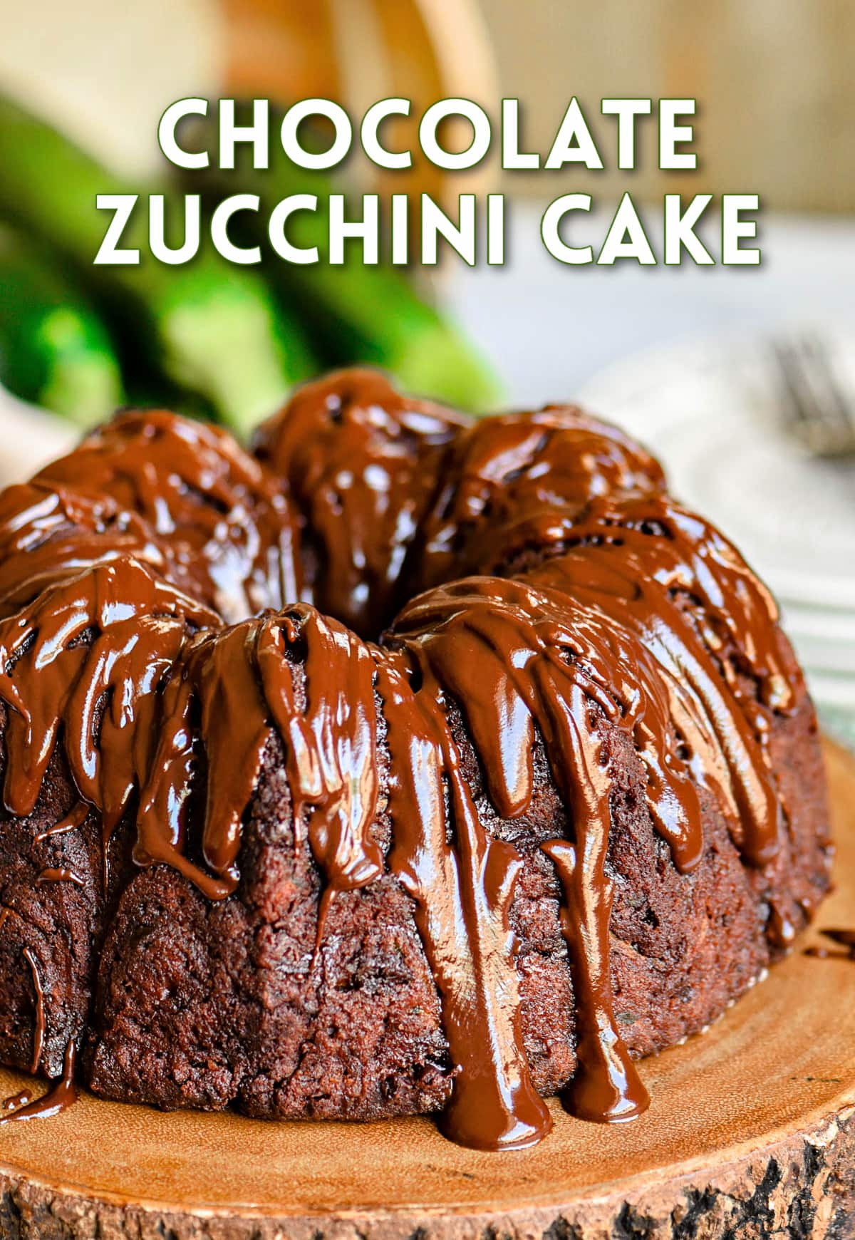 whole chocolate zucchini bundt cake on wood cake stand with rich chocolate glaze on top of cake.