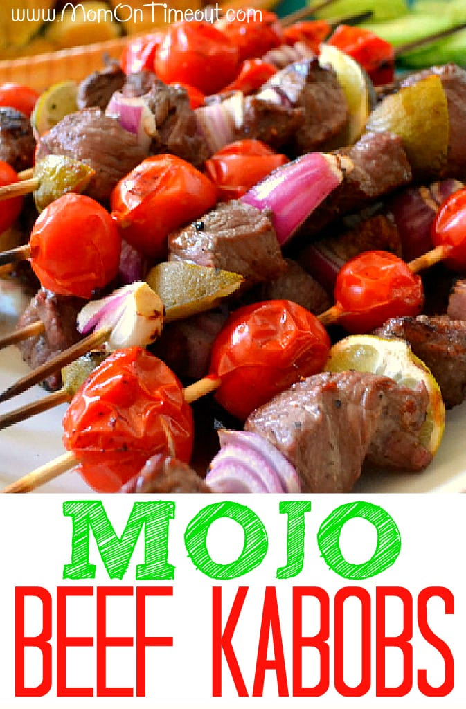 mojo beef kabobs on skewers on white plate with text overlay