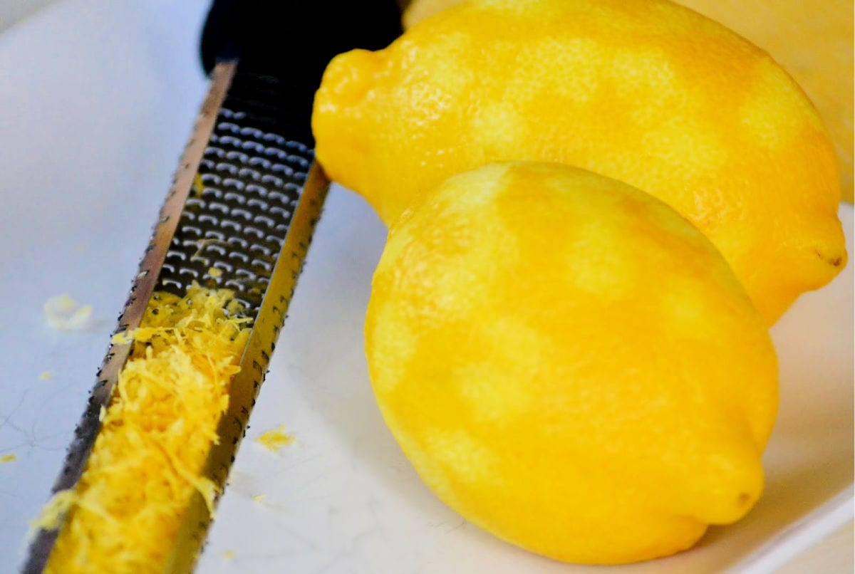 lemon being zested on white plate with microplane