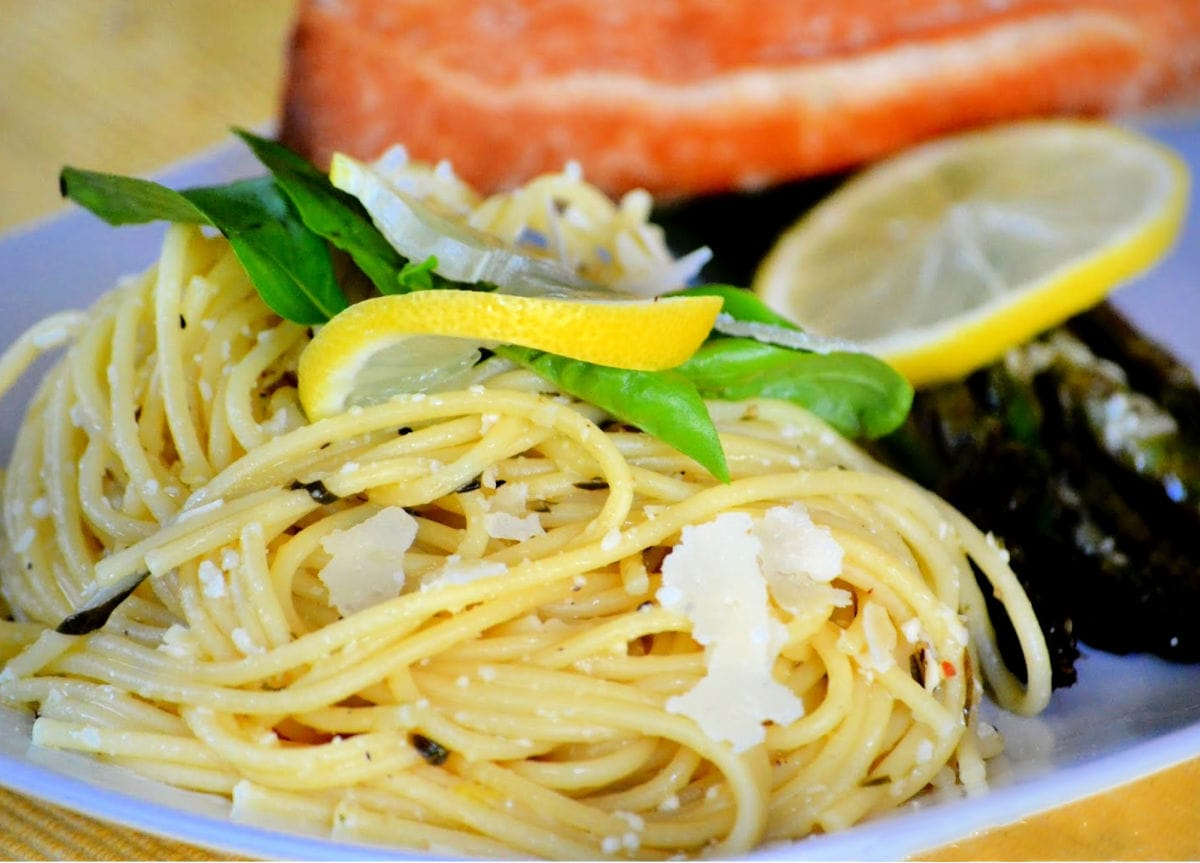 lemon spaghetti on white plate with asparagus and salmon garnished with lemon and basil and Parmesan