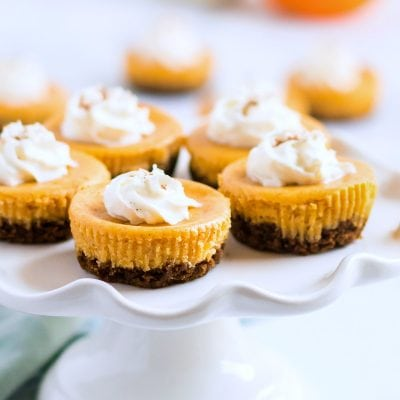 mini pumpkin cheesecake on white cake stand with title