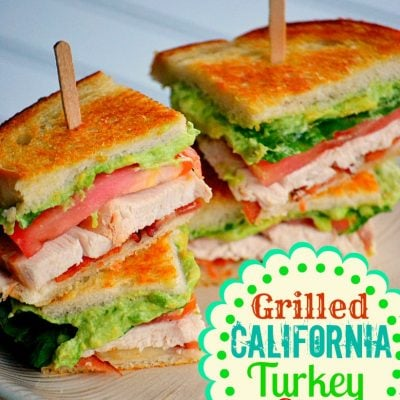 turkey club sandwich with avocado and bacon on small lunch plate