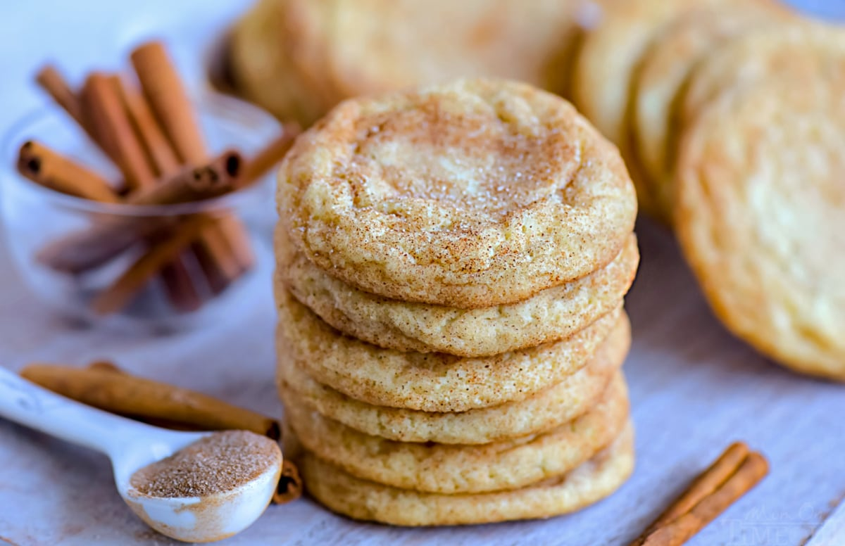 snickerdoodle cookies stacked on cutting board with cookies in background and cinnamon stick scattered around