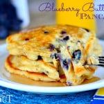 a stack of Blueberry Buttermilk Pancakes on white plate with syrup on a blue placemat