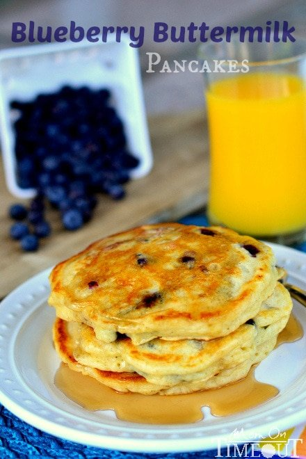 a stack of Blueberry Buttermilk Pancakes on white plate with syrup on a blue placemat and fresh blueberries in the background