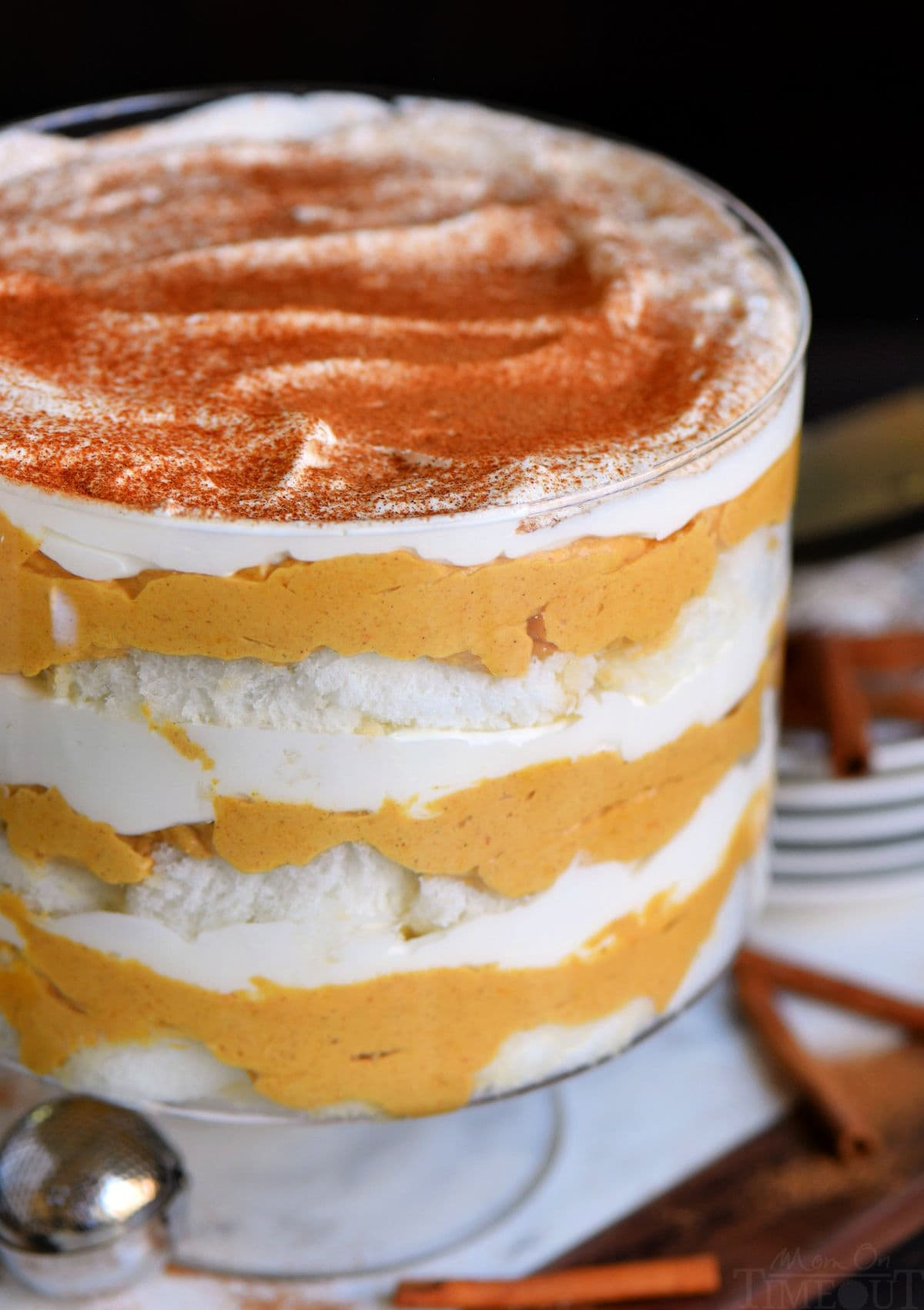 close up view of pumpkin cheesecake trifle in clear glass trifle dish topped with pumpkin pie spice.