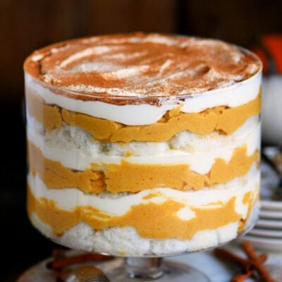 pretty pumpkin trifle in trifle dish with layers of pumpkin cheesecake, whipped cream and angel food cake.