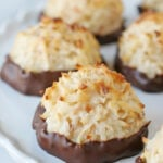 coconut macaroons dipped in chocolate on white cake stand
