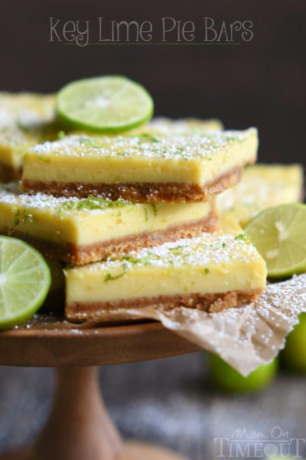 key lime pie bars stacked on a cake stand with lime slices