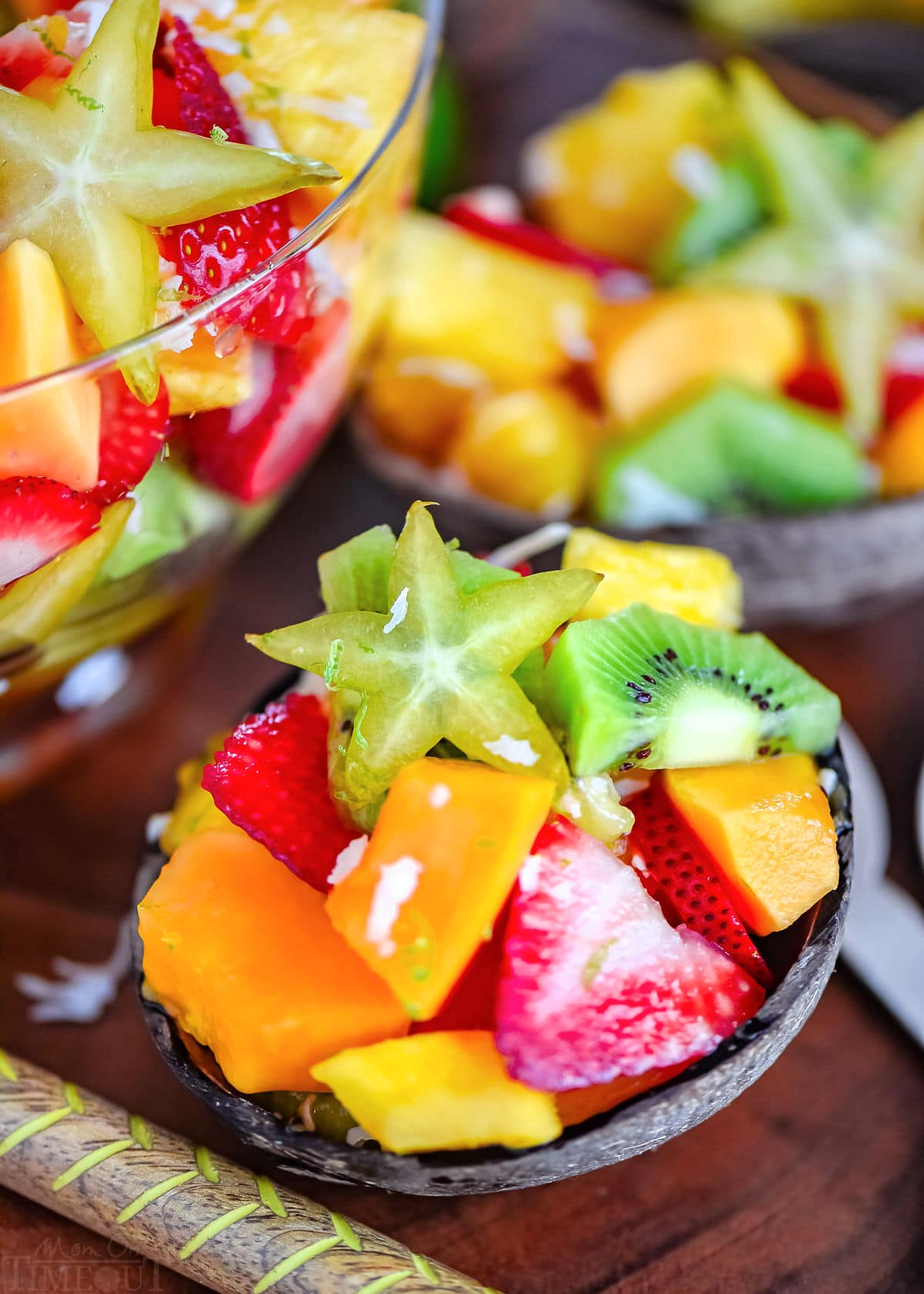 coconut half filled with tropical fruit salad. very brightly colored fruits.