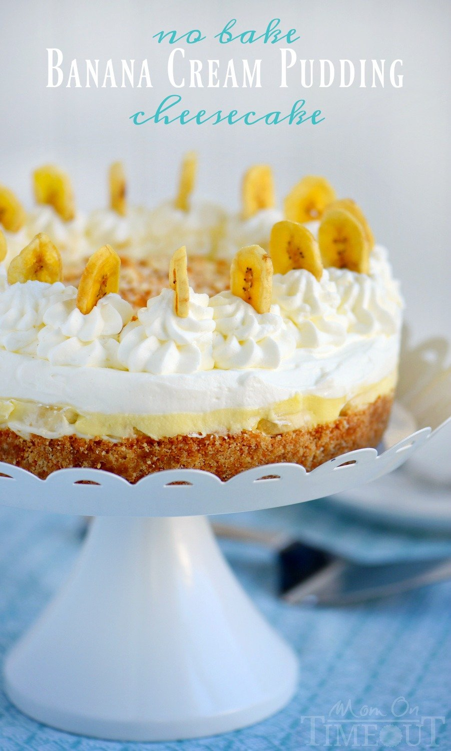 banana-cream-pudding cheesecake on white cake stand with banana chips for decoration