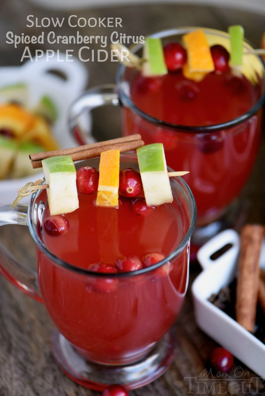 two glass mugs with cranberry apple cider on wood board with apple cranberry orange garnish