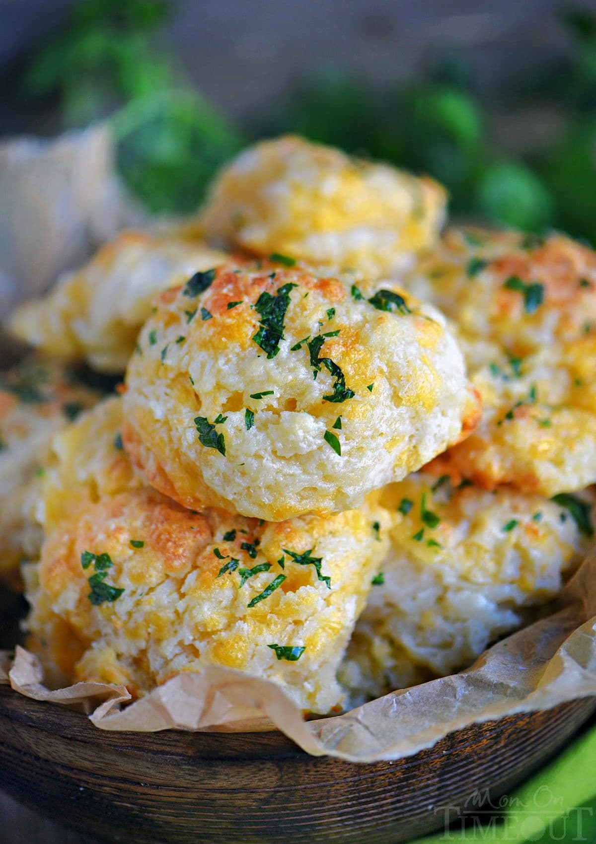 wood bowl filled with cheesy cheddar bay biscuits topped with a garlic herb butter.