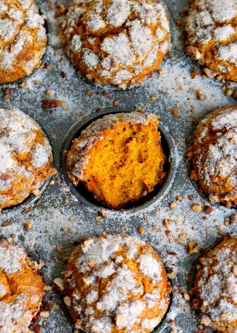 pumpkin muffins in muffin tin with sugar sprinkled around