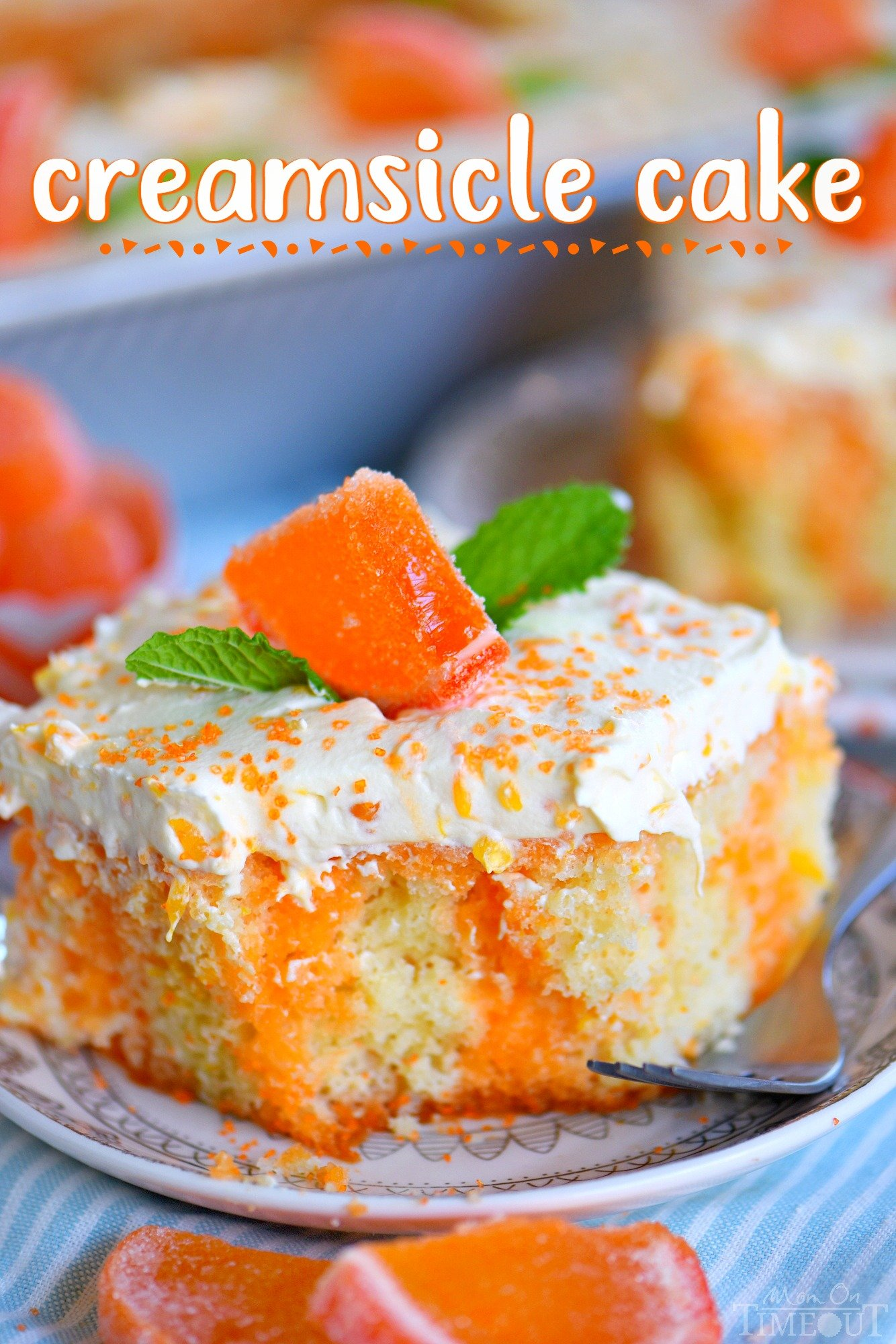 piece of orange creamsicle cake with mint leaves on small plate with fork