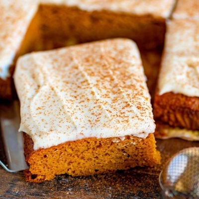 pumpkin bars cut into squares sitting on dark wood board with pumpkin pie spice dusted over the cream cheese frosting.