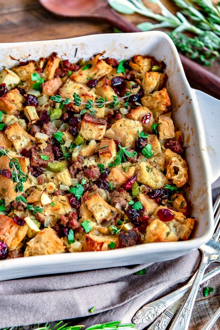 This easy Sausage Stuffing Recipe is our absolute favorite! Loaded with sausage, cranberries, apples and tons of fresh herbs it's the perfect addition to your holiday feast! // Mom On Timeout #sausagestuffing #stuffingrecipe #Thanksgiving #christmas #stuffing #recipe #dressing #sausage #cranberries #apple #sage #recipes #holidays