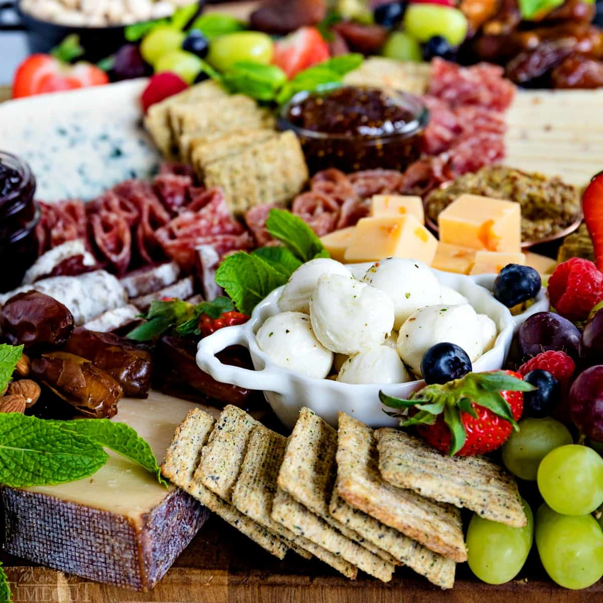 charcuterie-board-with-triscuit-crackers-mozzarella-balls-dates-grapes