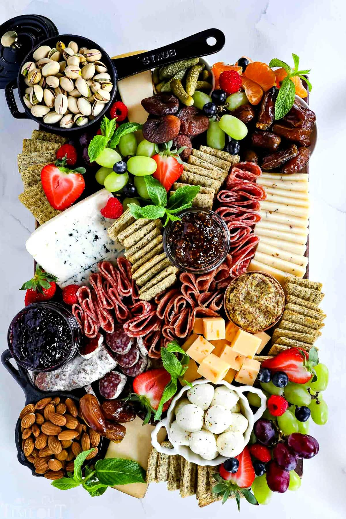 charcuterie-board-bowls-fruit-cheese-salami-nuts-crackers