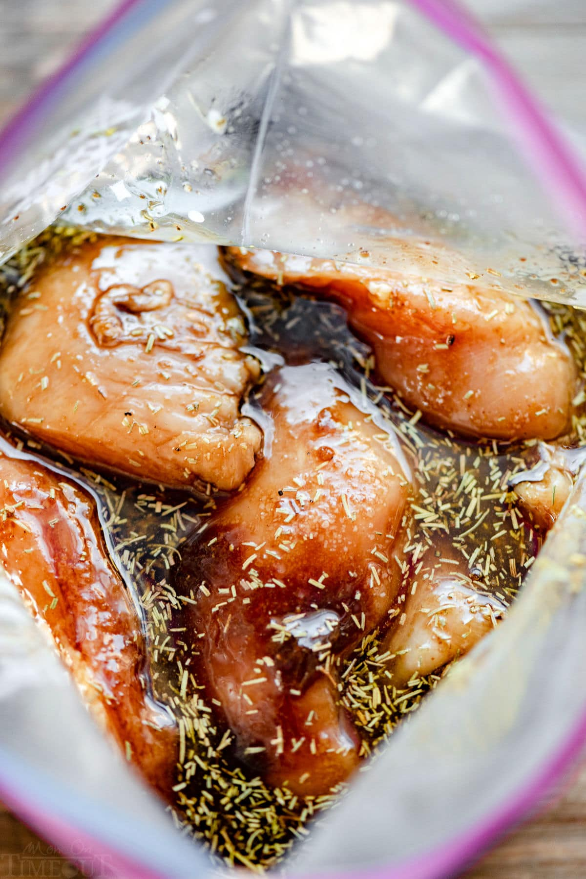 top down view of chicken marinating in large resealable bag.