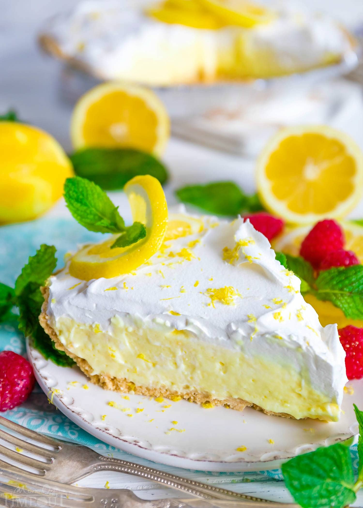 lemon pie with whipped cream topping on white plate.