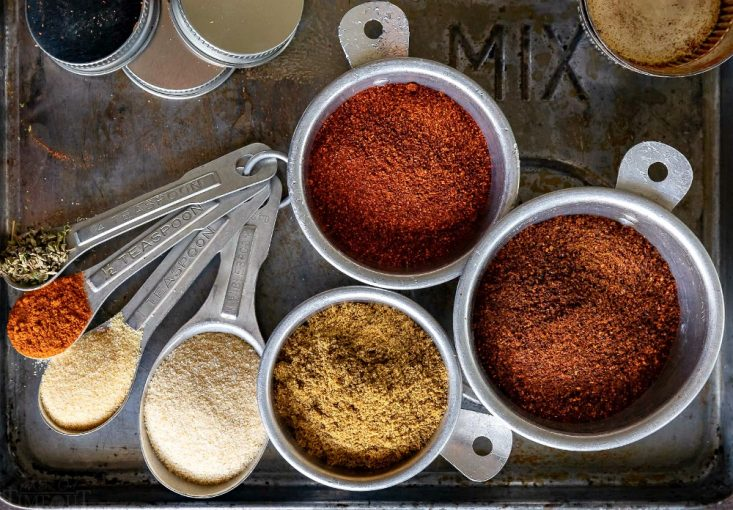 taco seasoning mix ingredients in measuring spoons and cups