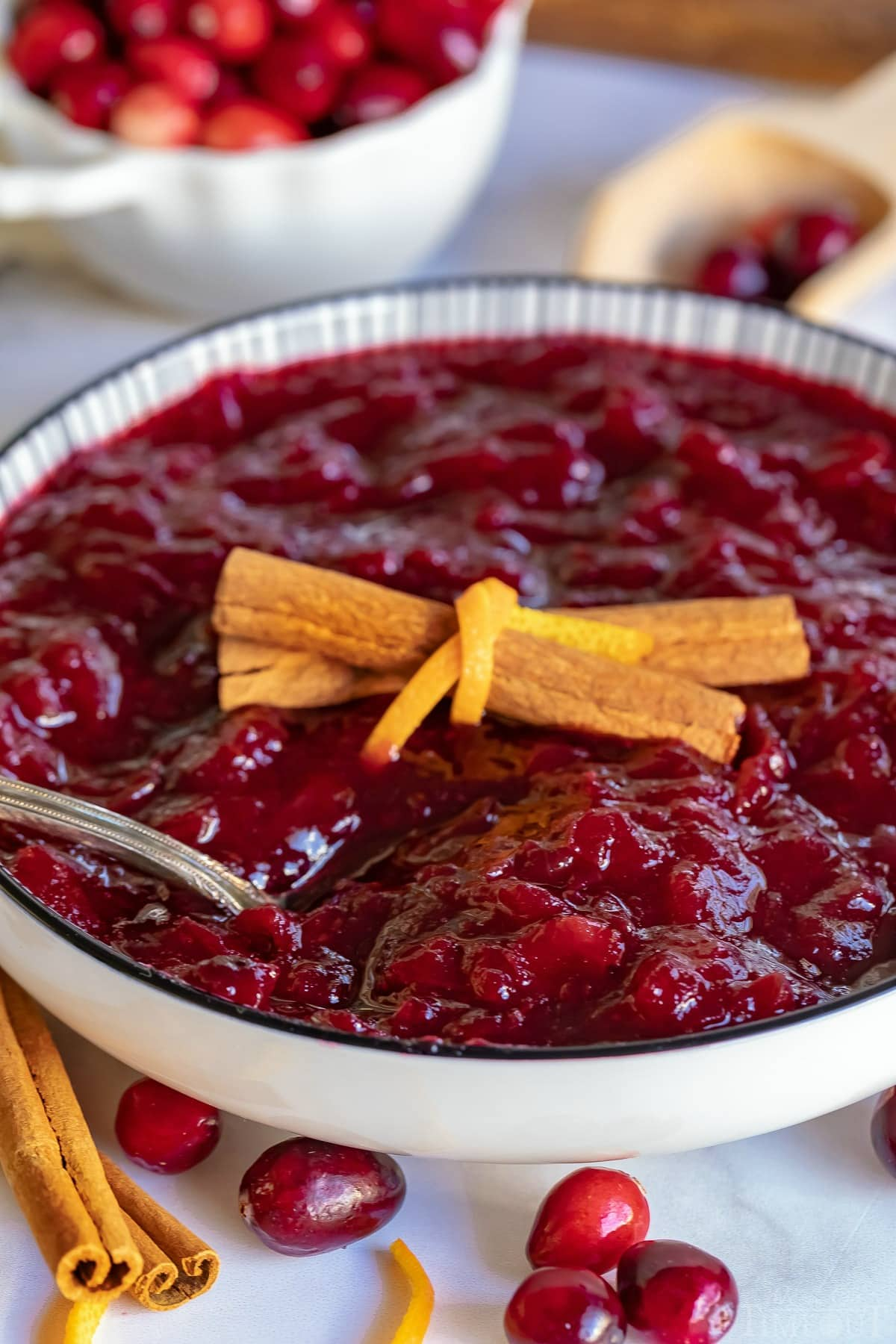cranberry sauce recipe in bowl garnished with cinnamon and orange peel