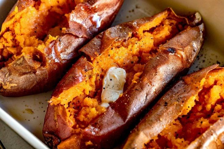 three baked sweet potatoes on sheet pan