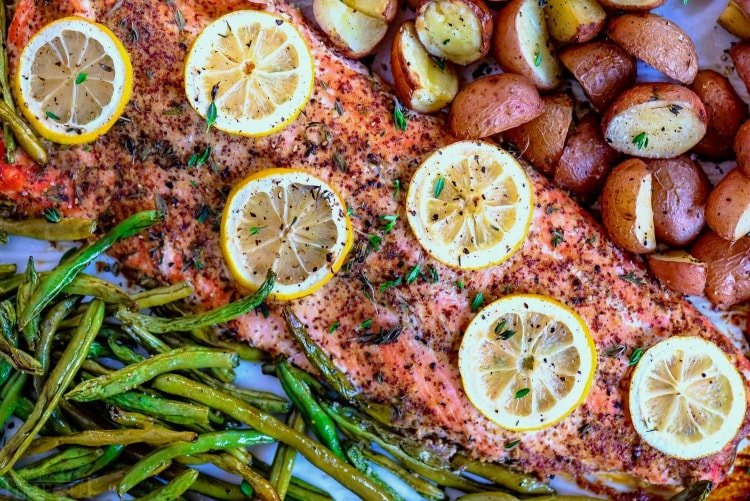 baked salmon recipe on a sheet pan with green beans potatoes and lemons