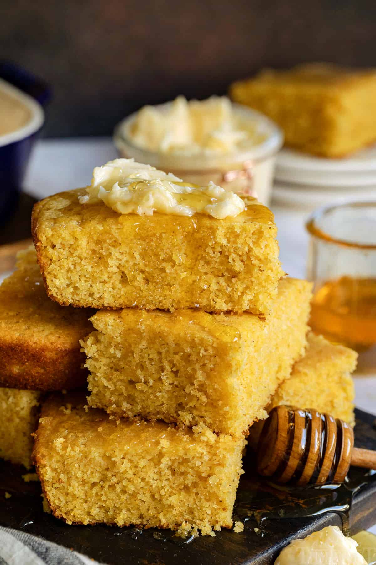 cornbread recipe stacked with honey drizzling and butter