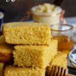 homemade cornbread stacked on a dark cutting board served with honey and butter