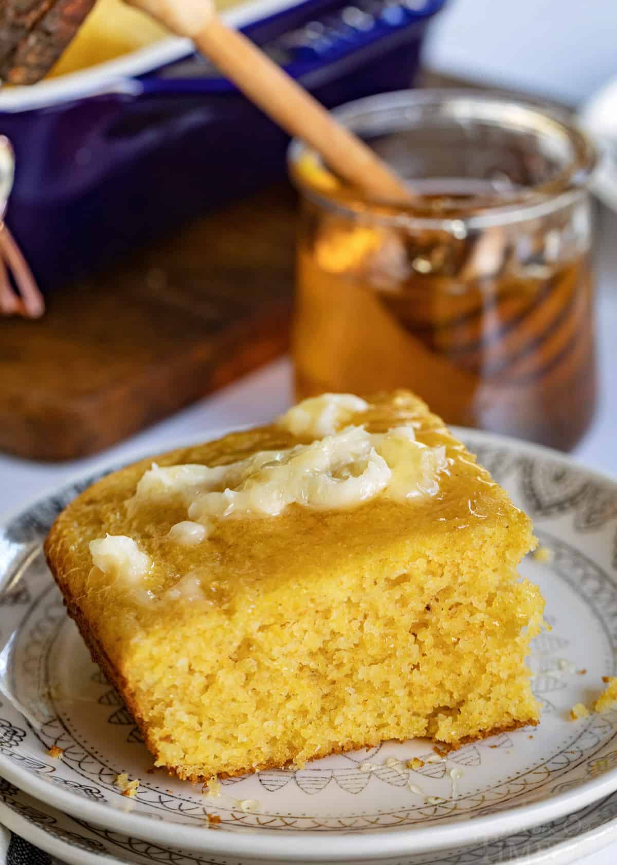 cornbread recipe piece on plate with honey butter and jar of honey in the background