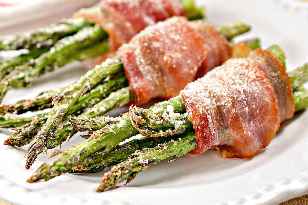 bacon wrapped asparagus plated on white plate