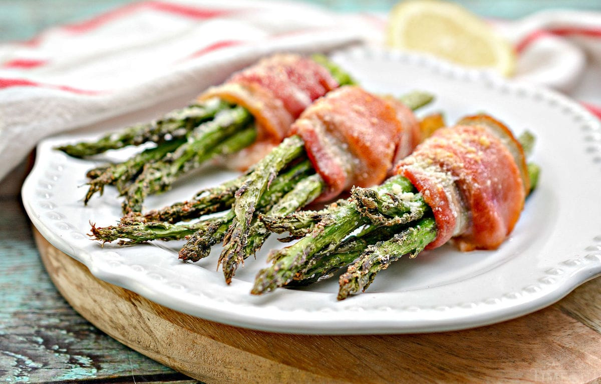bacon wrapped asparagus recipe on white plate on cutting board
