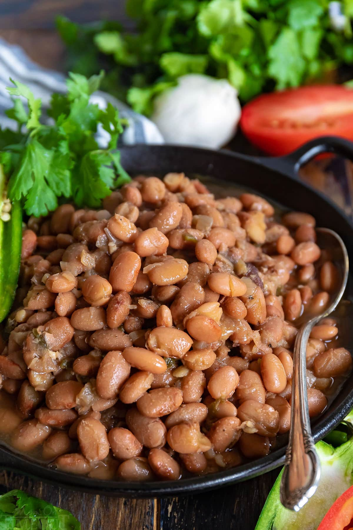 slow cooker pinto beans in black bowl with spoon and garnished with jalapeno and cilantro
