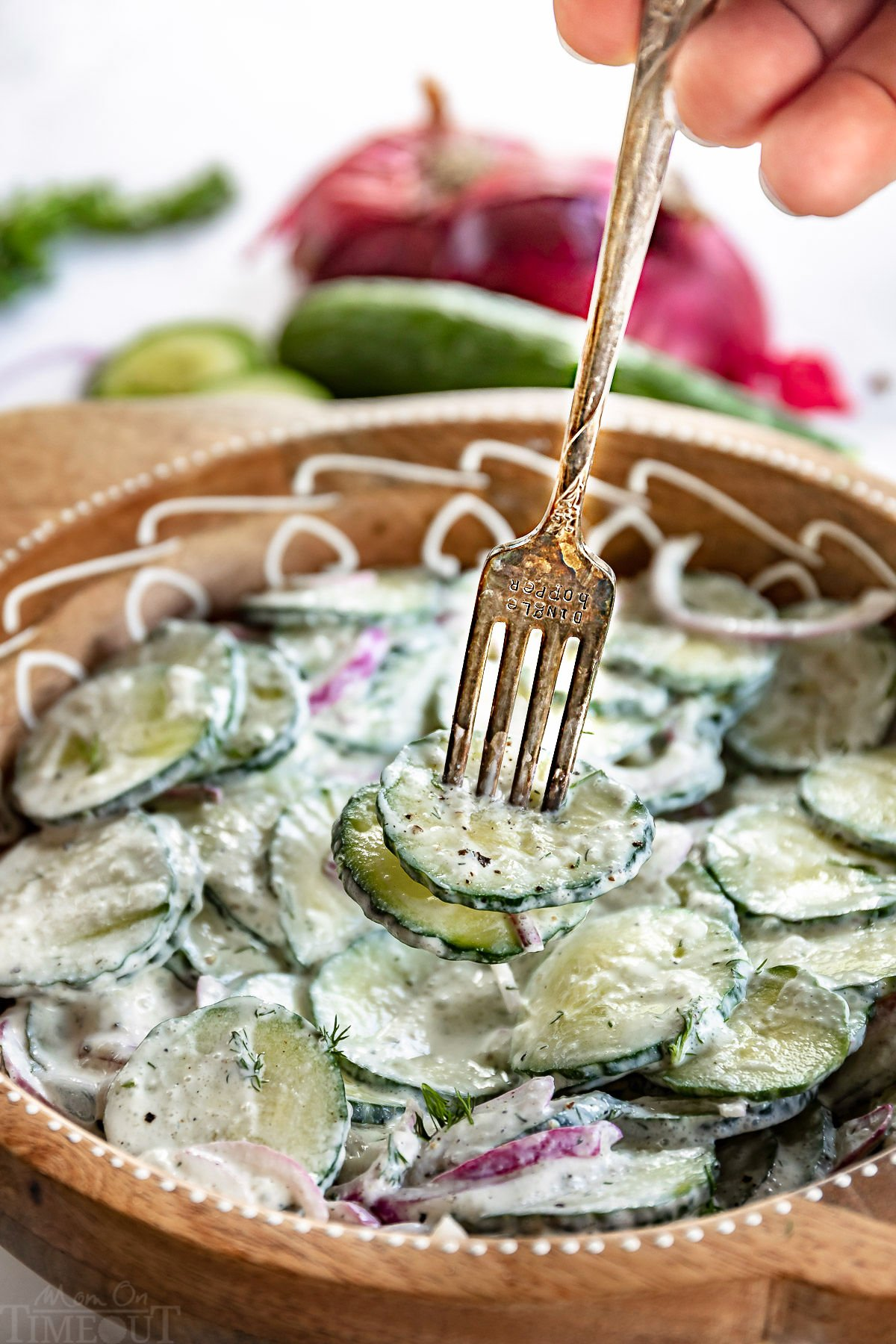 cucumber salad in large bowl with fork with two slices of cucumber on it