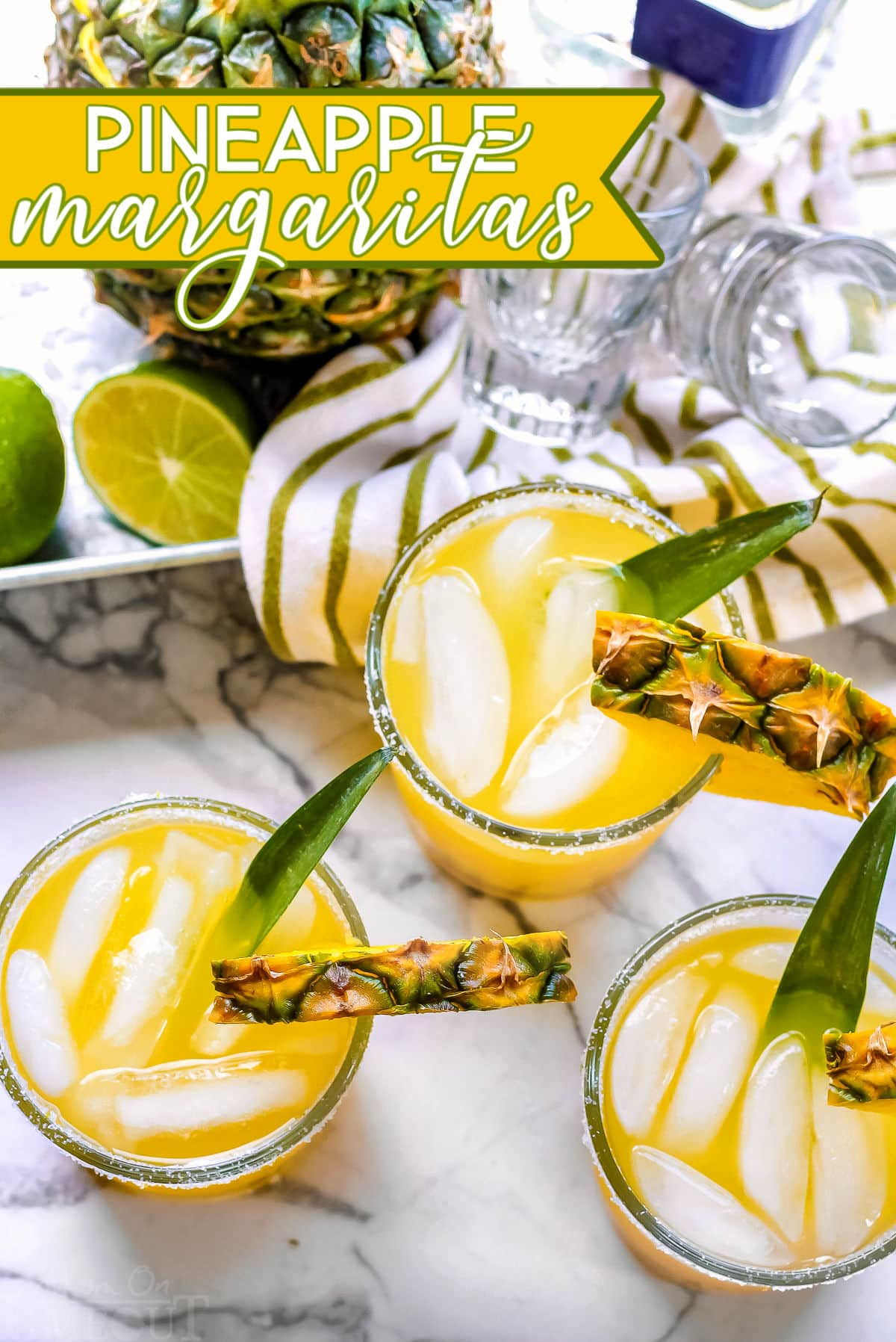 pineapple margaritas on marble cutting board with pineapple in the background and text overlay