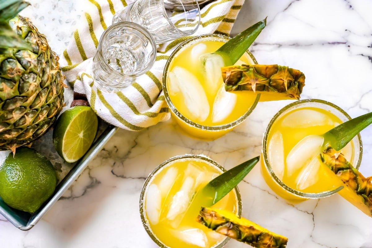 easy pineapple margarita recipe in glasses next to whole pineapple and limes on white marble backdrop
