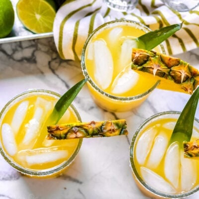 pineapple margaritas on marble cutting board with pineapple in the background square