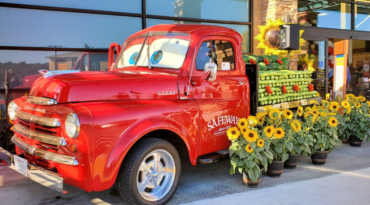 red safeway truck with produce on flatbed of truck in front of store