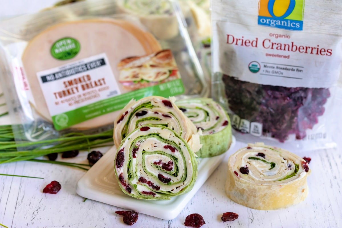 turkey cranberry pinwheels on small white board with packages of turkey meat and dried cranberries on the sides