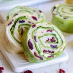 turkey pinwheels recipe with dried cranberries on small white cutting board squared