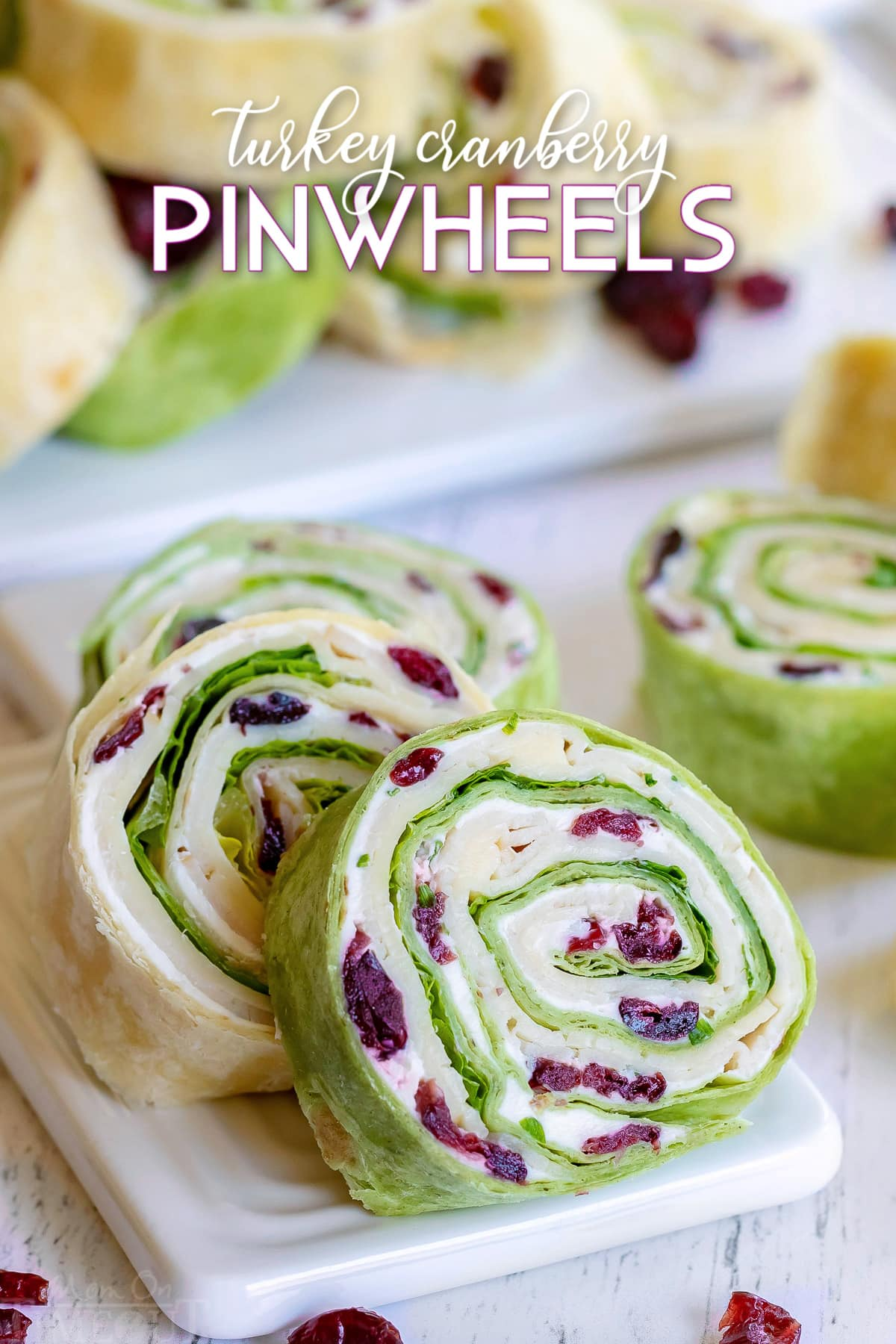 turkey pinwheels recipe with dried cranberries on small white cutting board