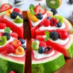 watermelon pizza recipe with a variety of fresh fruit on top cut into wedges on board square